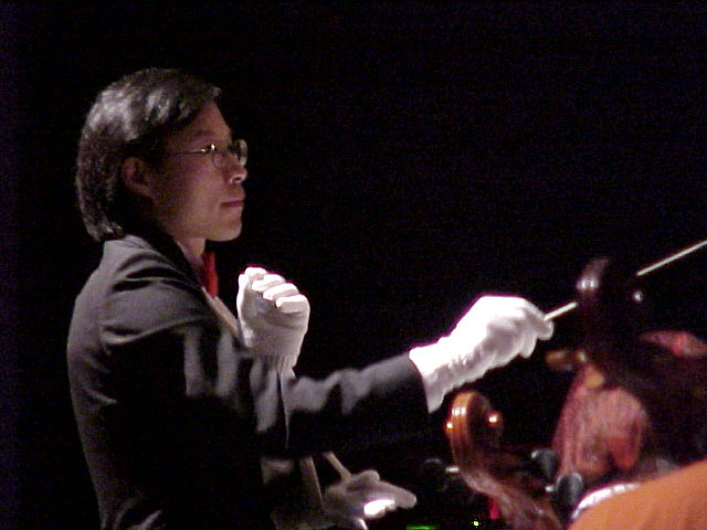 Maestro Michael Wen conducting the TSO with 3 arms